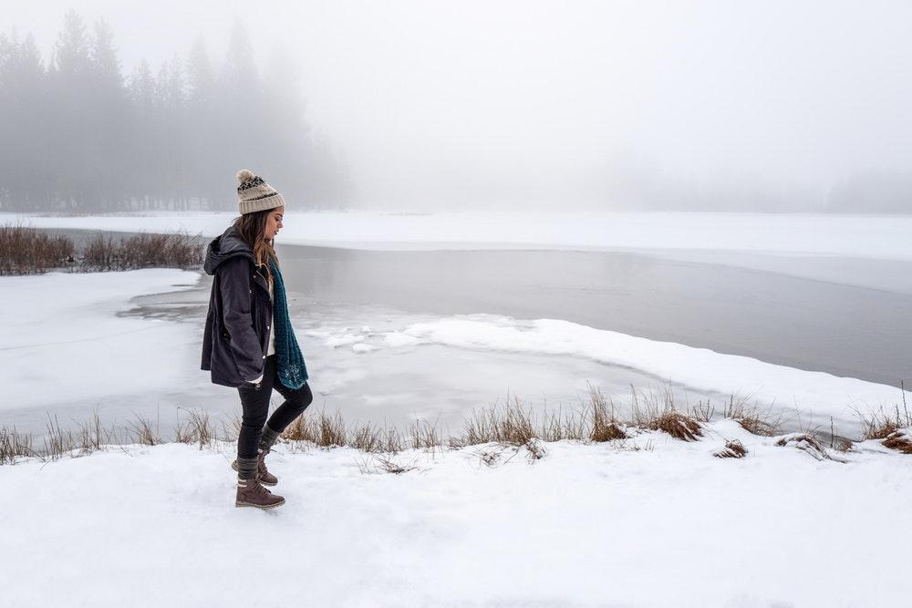 woman wearing black jacket walking on snow
