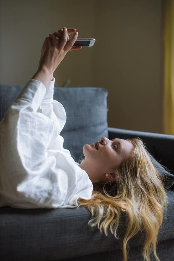 mulher loira deitada no sofá mexendo no celular