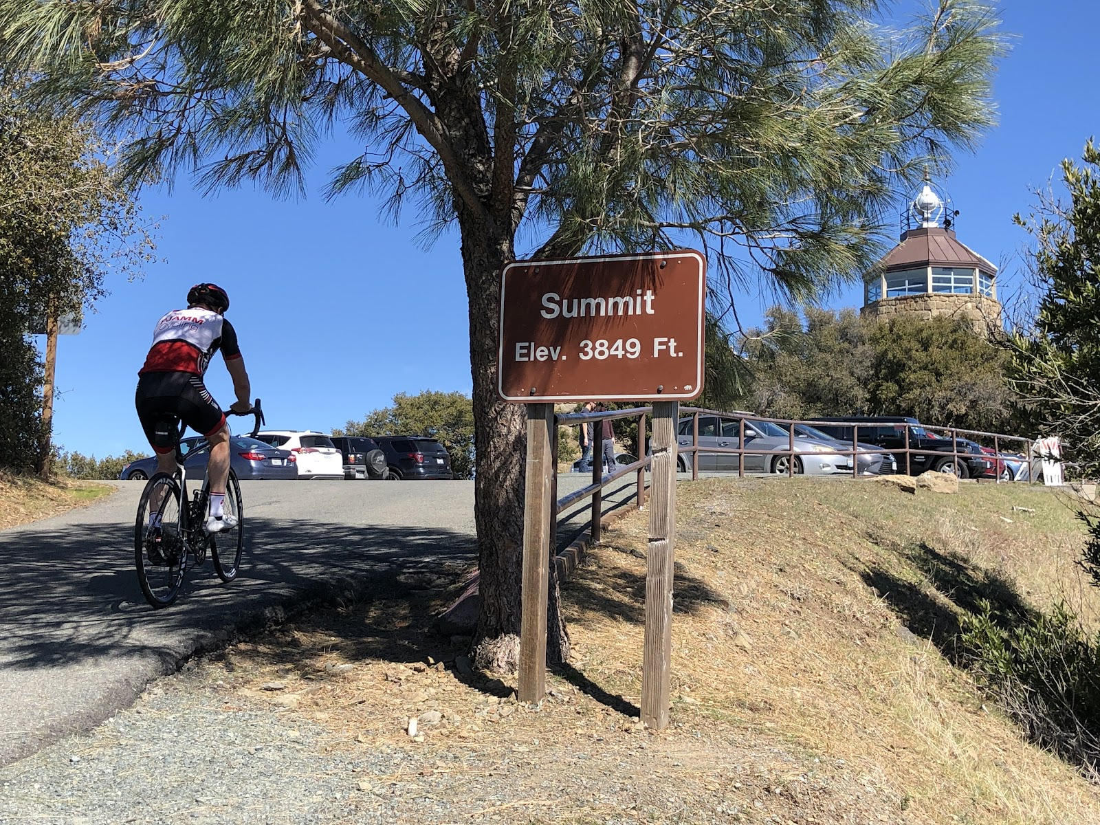 Cycling Mt. Diablo - cyclist on bike riding past summit sign - visitor center and beacon