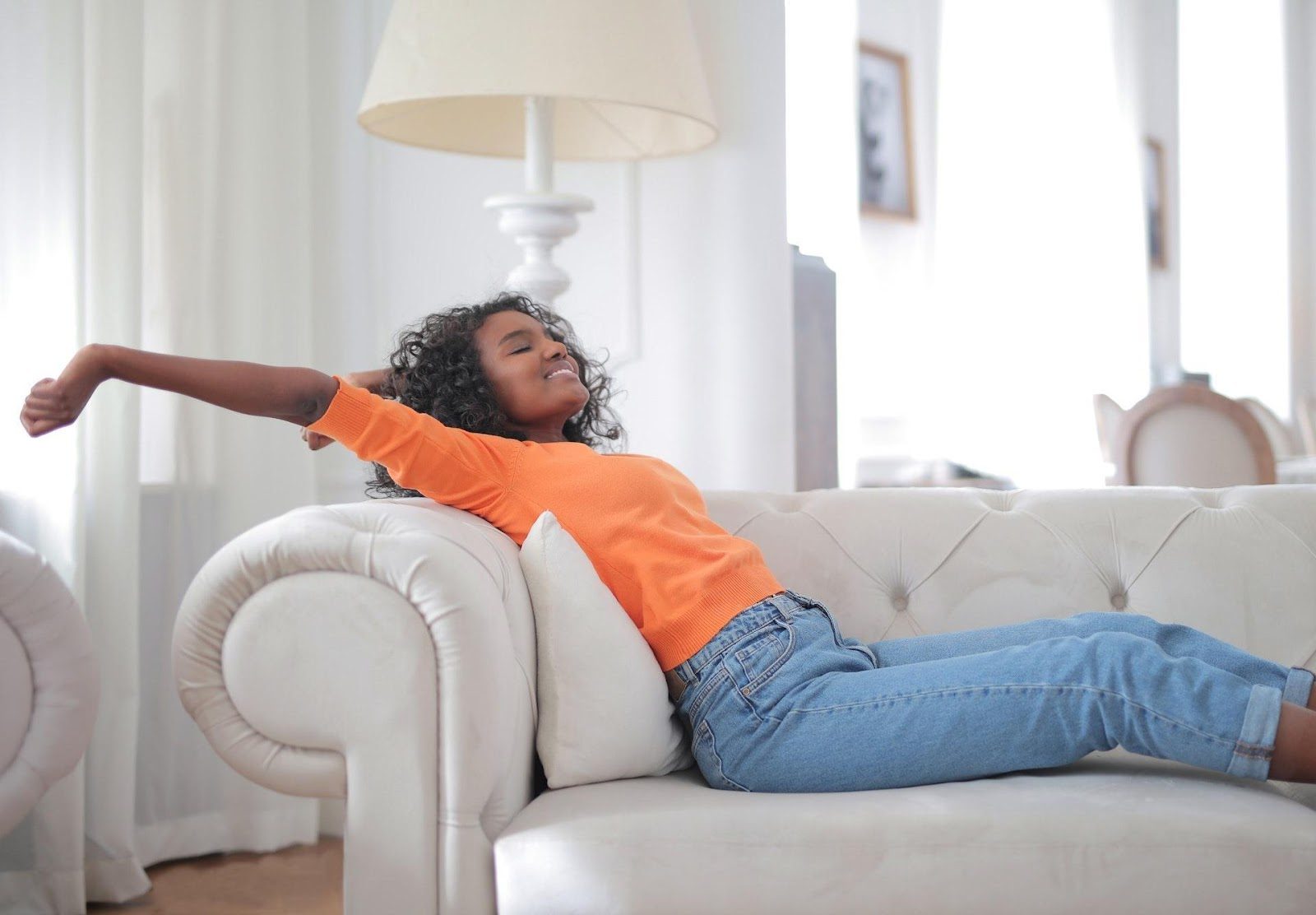 A woman sitting on a couch and smiling.