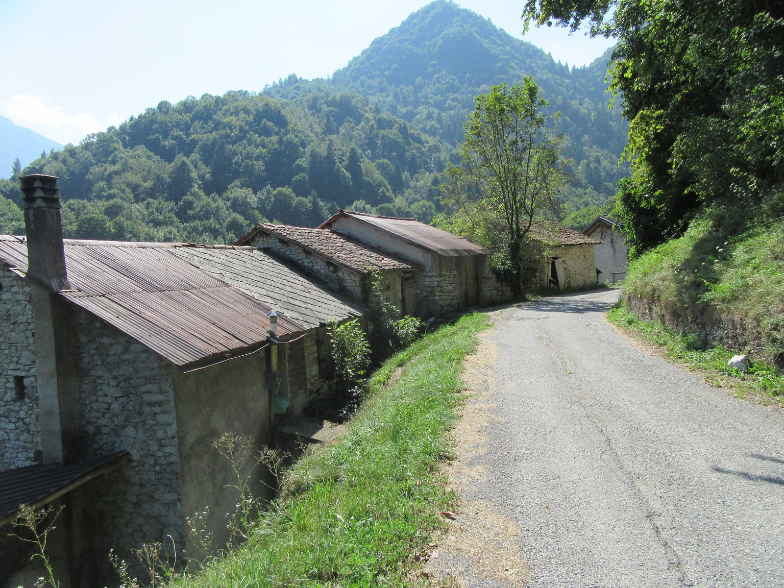 Biking up Monte Grappa from Seren - road and old buildings with mountains in background
