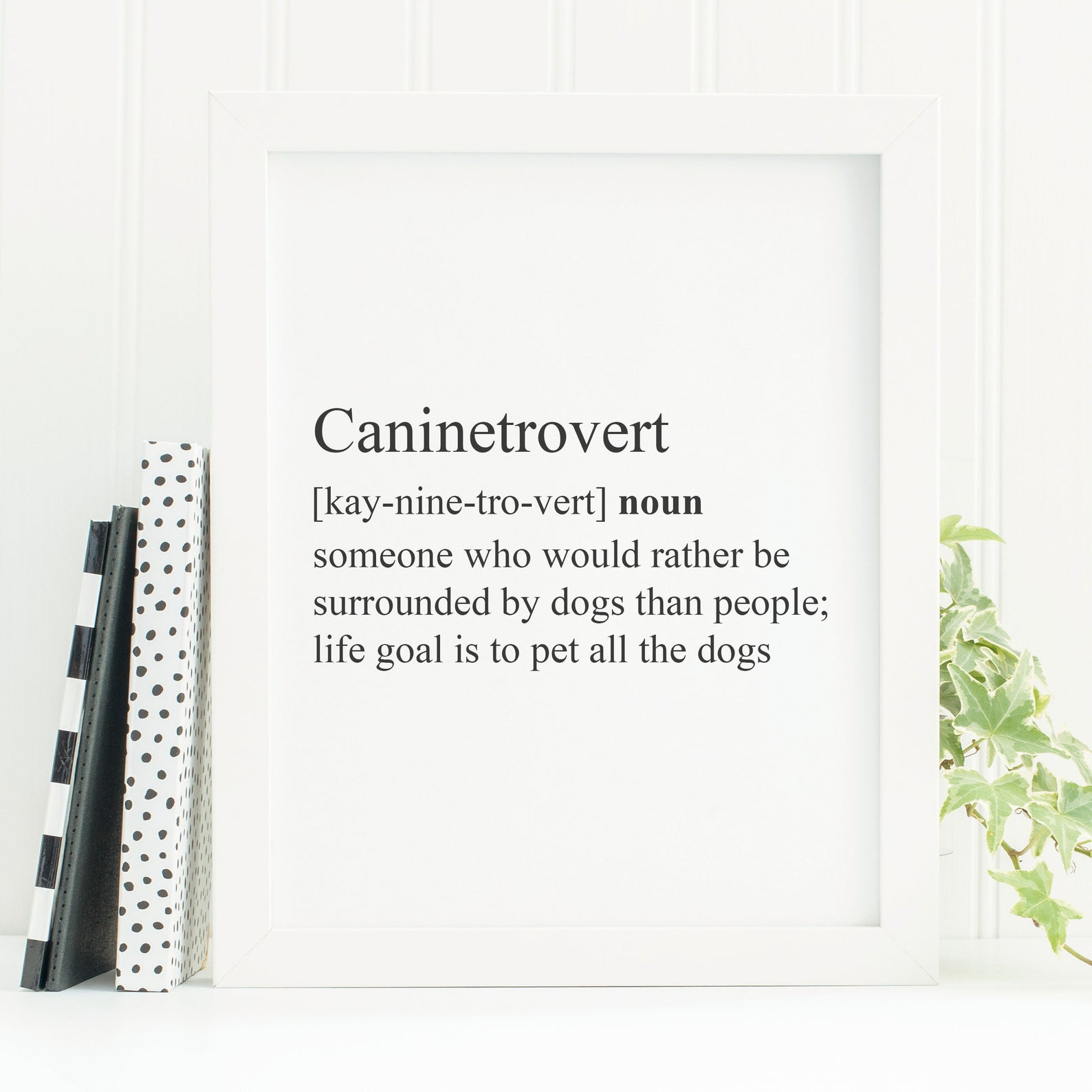 """Framed black and white print with a definition of a """"Caninetrovert,"""" which the print says is someone who'd rather be around dogs than people."""
