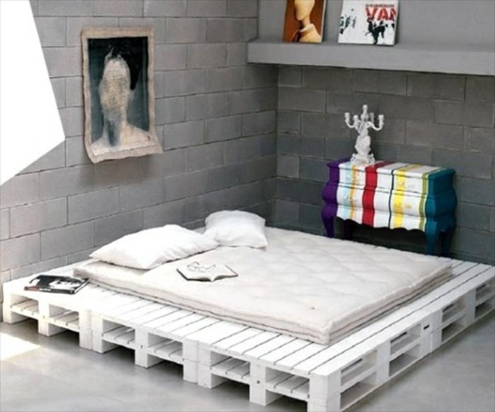 Кровать покрашенная в белый цвет и серые стены