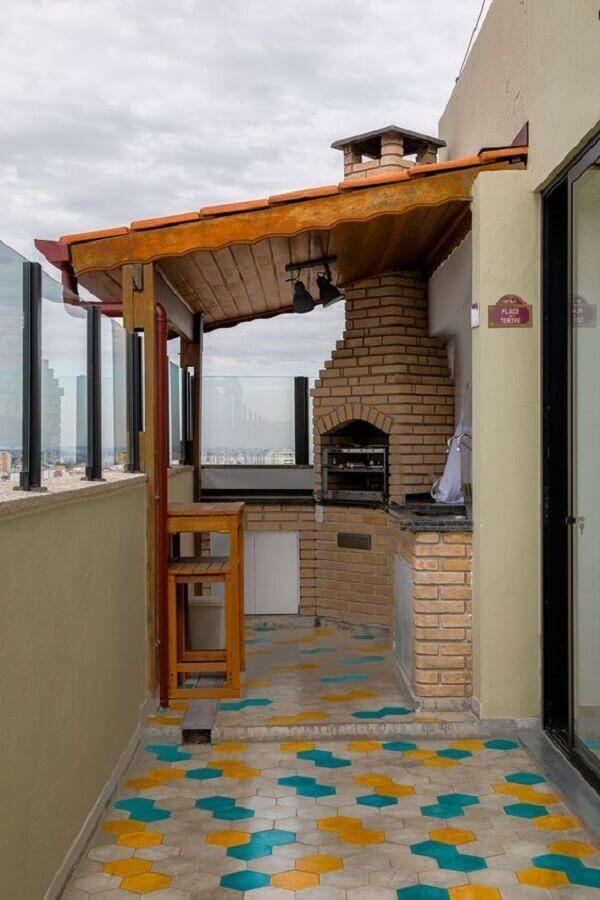 Varanda de apartamento com churrasqueira de tijolinhos, telhado de madeira e piso hexagonal colorido.